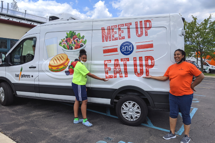 Two volunteers in front of the Meet Up and Eat Up van