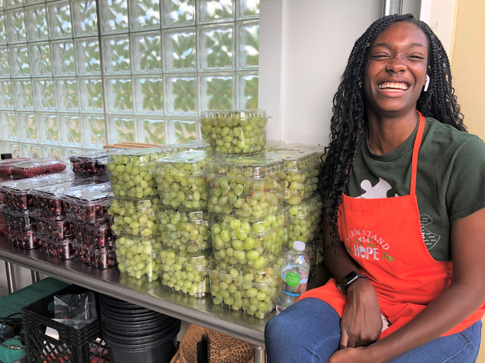 Woman smiling in front of a table of red and green grapes in packaging