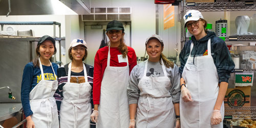 Volunteers in white aprons smile while working in Food Gatherers community kitchen