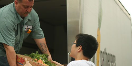 One volunteer puts a box of vegetables into another volunteer who is loading the Food Gatherers truck