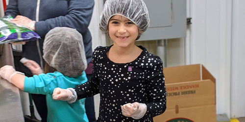 A child smiles while helping volunteer for Food Gatherers